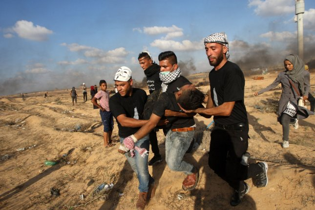 Palestinians carry the injured as Israeli forces fire tear gas at demonstrators during a protest demanding the right to return to their homeland at the Israel-Gaza border in the southern Gaza east Rafah on Friday. This is the 14th consecutive week of protests. Photo by Ismael Mohamad/UPI