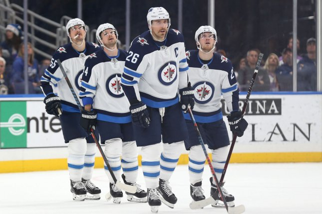 Winnipeg Jets forward Blake Wheeler skates to the bench after scoring a goal while teammates watch the replay against the St. Louis Blues in the first period on November 24 at the Enterprise Center in St. Louis. Wheeler scored a goal in the Jets' overtime win on Sunday. Photo by Bill Greenblatt/UPI
