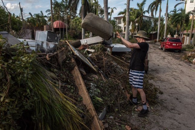 Mark Grafton throws away damaged items from his flooded house after Hurricane Irma struck in the Coconut Grove section of Miami in September 2017. File Photo by Ken Cedeno/UPI