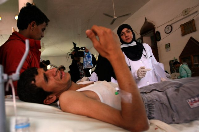 Doctors look after a wounded man at a makeshift hospital in Sana'a, Yemen. Wednesday's report documented at least 120 attacks on Yemeni hospitals and health workers over three years. File Photo by Mohammad Abdullah/UPI