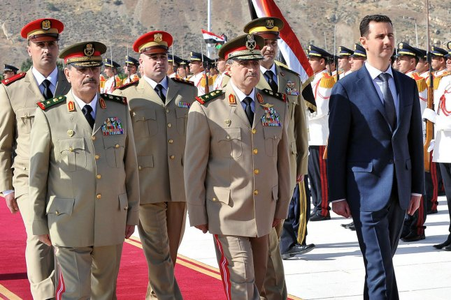 Syrian President Bashar al-Assad (R), Minister of Defense, Lt. Gen. Daoud Rajha and Chief of the General Staff, Gen. Fahid al-Freij attend a ceremony at the tomb of the unknown soldier in Damascus, Syria, in 2011. The U.N. Human Rights Council, in a report released Feb. 3, said an investigation has uncovered evidence indicating Assad's regime tortured and killed an untold number of detainees between 2011 and 2015 while they were in state custody. Photo by UPI