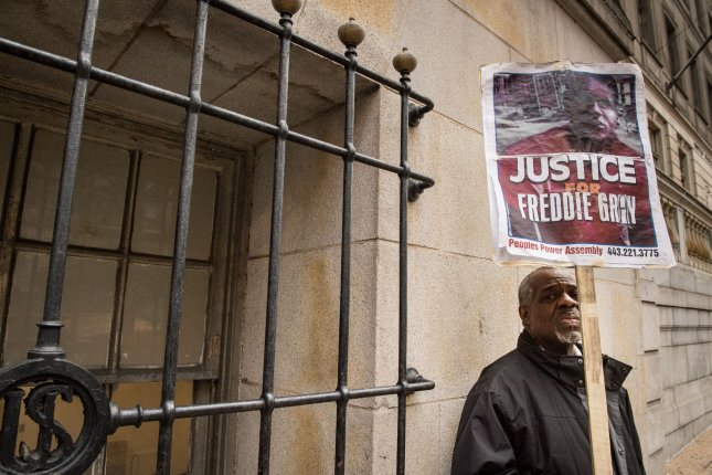 The trials for the police officers charged in the death of Freddie Gray, who died in April in police custody, have been delayed. Pictured: Arthur Johnson holds up a sign in front of the Baltimore City Courthouse as jury deliberations continue in the trial against Baltimore Police officer William Porter in Baltimore, Maryland December 16, 2015. Porter is the first of six police officers to be tried in death of black detainee Freddie Gray from injuries sustained while in police custody. Gray, 25, died a week after suffering a spinal cord injury while being arrested on April 12, 2015. Photo Ken Cedeno/UPI