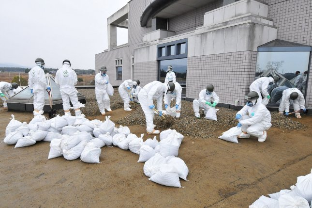 Members of Japan's Ground Self Defense Force decontaminate at the city office of Tomioka Machi, 5 1/2 miles from the Fukushima Dai-ichi nuclear power plant in Fukushima prefecture, Japan, on December 8, 2011. The earthquake occurred on March 11, 2011. For the first time, radiation reached North America earlier this year. File photo by Keizo Mori/UPI
