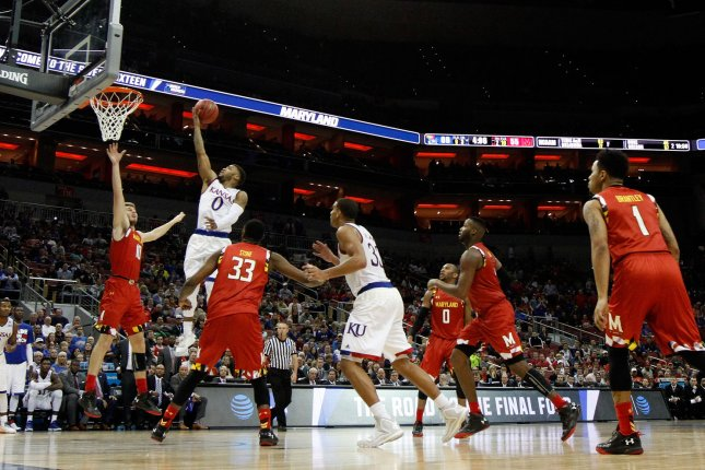 University of Kansas' Frank Mason (0) fights to get his shot off under pressure from University of Maryland's Jake Nickens (10) during the second half of play in their fourth round of the 2016 NCAA Division I Men's Basketball Regional Championship game at the KFC Yum! Center in Louisville, Kentucky, March 24, 2016. File photo by John Sommers II/UPI