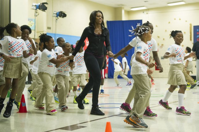 Former first lady Michelle Obama exercises with students at a Washington, D.C., elementary school during a health-related event. The United States was among the nations that reported a decrease in child physical inactivity in the WHO study. File Photo by Kevin Dietsch/UPI