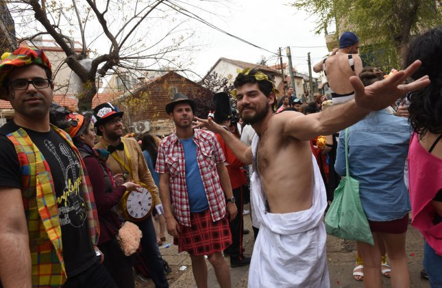 Israelis wear costumes to celebrate the Jewish holiday of Purim in Jerusalem on March 25, 2016. Why the costumes? And why do some kids smoke and their parents drink until they're drunk? Photo by Debbie Hill/ UPI