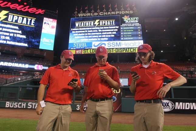 Busch Stadium grounds crew members check radar on their cell phones as they await the strong storms, causing the cancellation of the San Diego Padres-St. Louis Cardinals baseball game at Busch Stadium in St. Louis on July 19, 2016. Photo by Bill Greenblatt/UPI