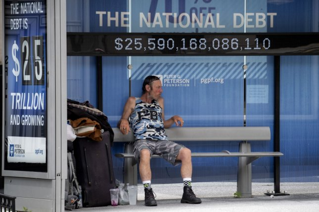 A man sits at a bus stop displaying the national debt in downtown Washington, D.C., a few blocks from the White House, on May 29. File Photo by Pat Benic/UPI