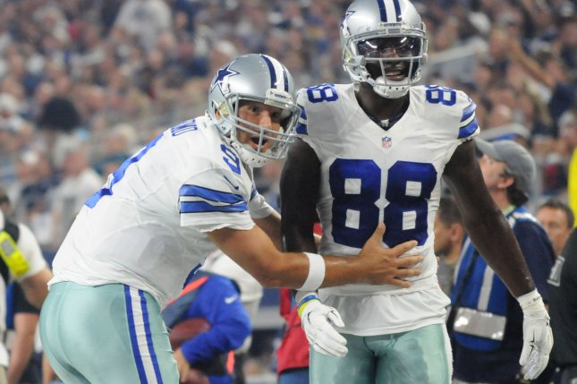 Dallas Cowboys QB Tony Romo, left, demonstrates the holding call he wanted on teammate Dez Bryant during the first half against the New York Giants at AT&T Stadium on September 13, 2015 in Arlington, Texas. UPI/Ian Halperin