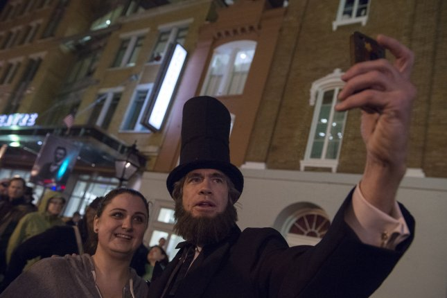 David Selby, dressed as Abraham Lincoln, greets people in front of the Ford's Theatre in Washington, D.C., April 14, 2015. Visitors and period actors took part in a candle light vigil to commemorate 150 years since the shooting of President Lincoln. Photo by Molly Riley/UPI