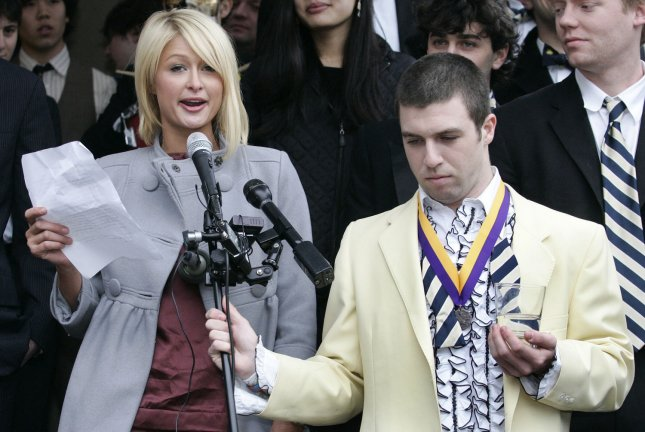 Paris Hilton addresses the crowd before she was presented with the Harvard Lampoon Woman of the Year award at Harvard University in Cambridge, Massachusetts on Feburary 6, 2008. Holding the microphone stand is Harvard student Garrett Schabb a member of the Lampoon. (UPI Photo/Matthew Healey)