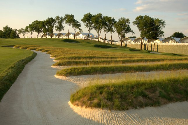 The sun sets on famous Oakmont Church Pews bunkers between the third and fourth fairways, at the Oakmont Country Club in Pennsylvania. Oakmont is hosting the U.S. Open for a record ninth time. Photo by Kevin Dietsch/UPI