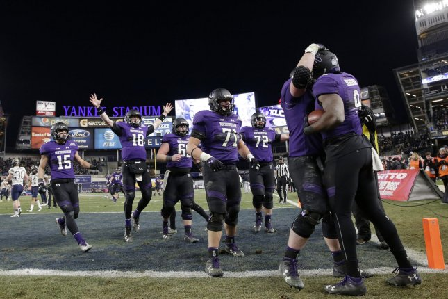 Former Northwestern Wildcats tight end Garrett Dickerson (9) celebrates with teammates after he scores a touchdown in the second half against the Pittsburgh Panthers during the Pinstripe Bowl on December 28, 2016 at Yankee Stadium in New York City. File photo by John Angelillo/UPI