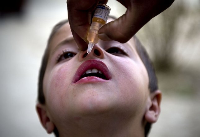 An Afghan child looks on as a health worker administers polio vaccine on the second day of a vaccination campaign in Kabul on March 15, 2010. Photo by Hossein Fatemi/UPI