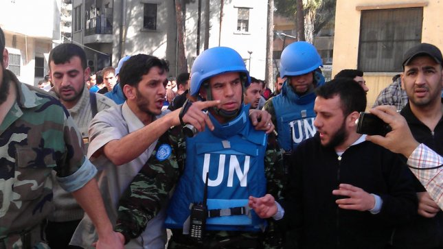 Syrian Abdul Razzaq Tlas (L),leader of the opposition Katibat al-Faruq, walks with Moroccan UN observer, Colonel Ahmed Himmiche (C), during the United Nations monitors visit to the restive city of Homs, Syria on April 21, 2012. UPI/Khaled Tallawy