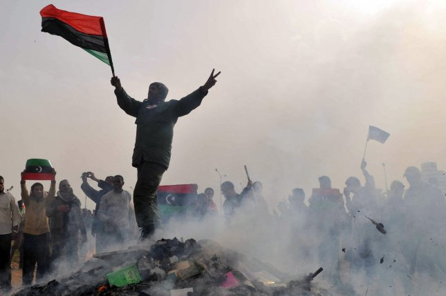 A Libya national stands atop a burning heap of books authored by leader Moammar Gadhafi at a local park in Benghazi, Libya, on March 2, 2011. A week earlier, then-U.S. President Barack Obama imposed new sanctions against Gadhafi's regime, which were extended by President Donald Trump Friday. File Photo by Mohamaad Hosam/UPI