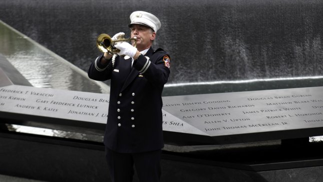 A firefighter plays taps at the National September 11 Memorial at the World Trade Center site in New York, Sunday, Sept. 11, 2011. UPI/Seth Wenig/POOL