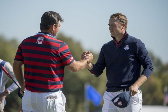 USA team member Jordan Spieth (R) shakes hands with teammate Patrick Reed after the two tied their match against the Europeans on the 18th green on day 2 of the 2016 Ryder Cup at Hazeltine National Golf Club in Chaska, Minnesota on October 1, 2016. Photo by Kevin Dietsch/UPI