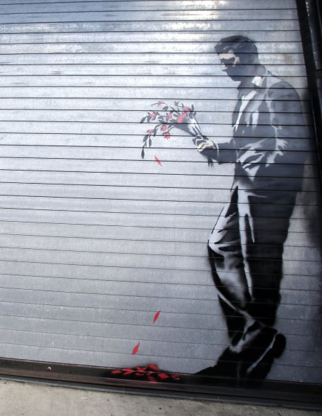 Waiting in vain...at the door of the club, an art work created by British street artist Banksy, can be seen on a security gate outside of the Hustler Club in New York City on October 24, 2013. Banksy is a pseudonymous England-based graffiti artist, political activist, film director, and painter. His satirical street art and subversive epigrams combine dark humor with graffiti done in a distinctive stenciling technique. UPI/John Angelillo