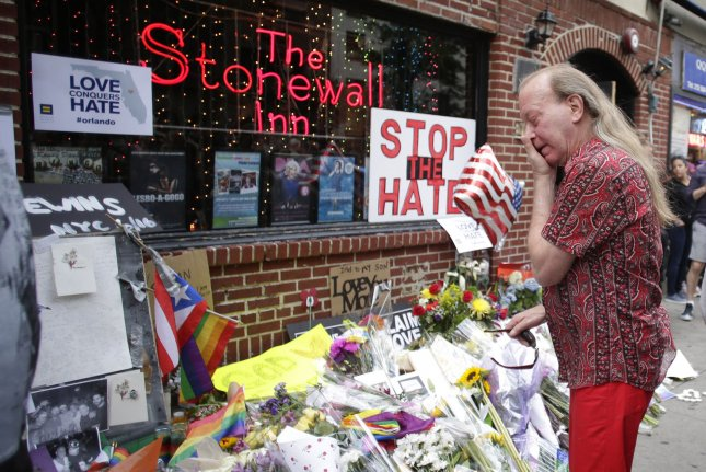 A man wipes tears from his eyes Monday while looking at a memorial for the victims of the mass shooting at an Orlando, Fla., gay club outside of The Stonewall Inn in New York City. The historic gay bar is one of dozens of destinations to and from which Uber is offering free rides this weekend. Photo by John Angelillo/UPI