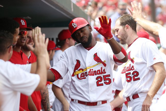 St. Louis Cardinals' Dexter Fowler slaps hands with teammates in the dugout. File photo by Bill Greenblatt/UPI
