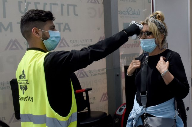 A security guard checks the temperature of a woman, as a precaution for COVID-19, before granting her entrance to the Rami Levy Atarot Mall, north of Jerusalem, on Thursday. Photo by Debbie Hill/UPI