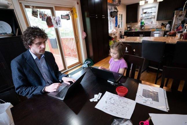 Economist Gray Kimbrough works at home in April 2020 alongside his daughter Violet, who was participating in distance learning from her school. New research suggests that entirely home-based workforces can limit communication and collaboration that comes from being together in an office. File Photo by Kevin Dietsch/UPI