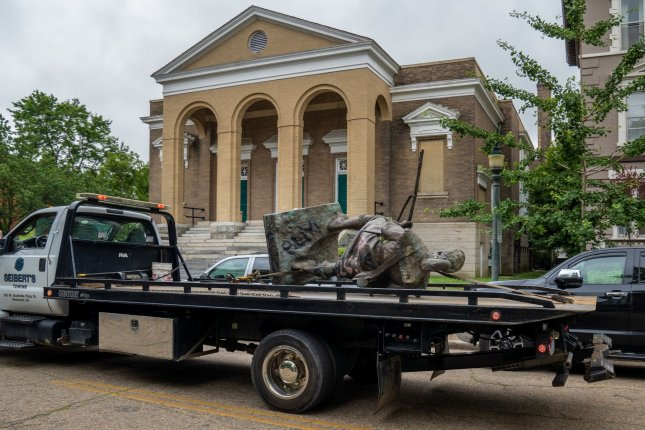 The statue of a militia man is hauled away from the nearby General Robert E. Lee monument prior to a rally set for later Saturday in Richmond, Va. Photo by Ken Cedeno/UPI