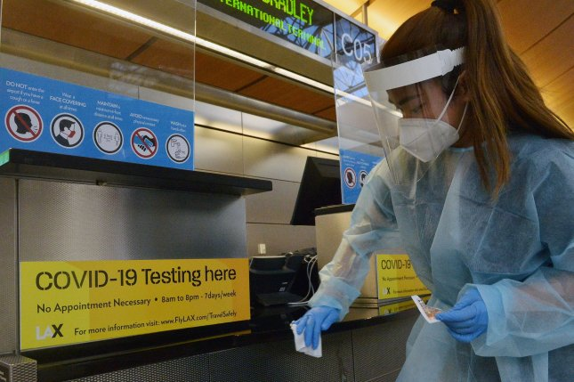 A worker disinfects a counter in the Tom Bradley International Terminal at Los Angeles International Airport last Wednesday. Coronavirus cases in Los Angeles County have tripled over the past month. Photo by Jim Ruymen/UPI