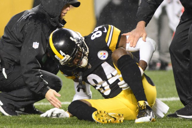 Pittsburgh Steelers wide receiver Antonio Brown (84) reaches for his leg in pain and leaves the game in the second quarter against the New England Patriots on December 17, 2017 at Heinz Field in Pittsburgh. Photo by Archie Carpenter/UPI