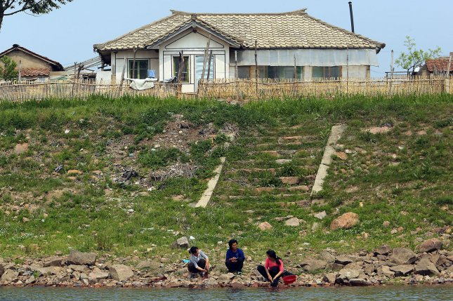 North Korean women wash clothing on the banks of the Yalu River near Sinuiju, across the Yalu River from Dandong, China's largest border city with North Korea. Such activities had been banned during the Seventh Party Congress, a North Korea source said. File Photo by Stephen Shaver/UPI