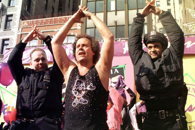 Richard Simmons convinces New York Police officers to join an impromptu exercise session on February 10, 2000. Simmons has thanked hospital staff and police officers after he was hospitalized for three days. File Photo by Ezio Petersen/UPI