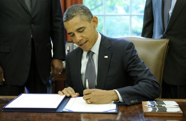 U.S. President Barack Obama signs the renewal of Trade Adjustment Assistance for workers in the Oval Office of the White House in Washington, DC, on October 21, 2011. The bill helps workers whose jobs get moved over seas. UPI/Roger L. Wollenberg