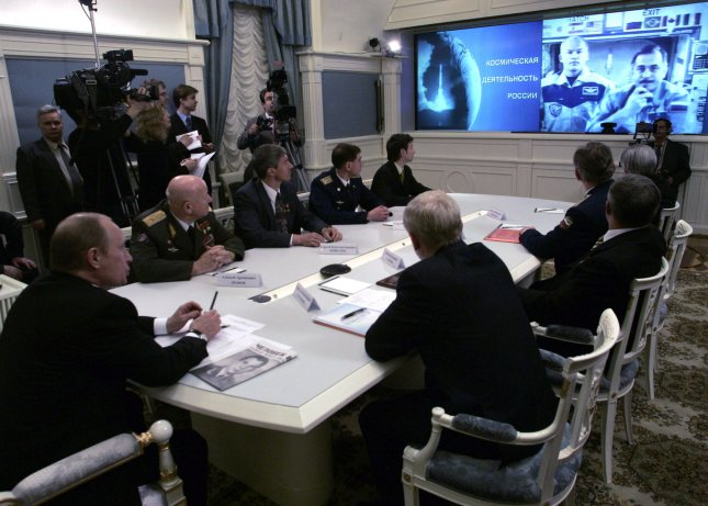 Astronaut Jeff Williams (L) and Russian cosmonaut Pavel Vinogradov are shown on the screen during a video-phone linkup from the International Space Station April 12, 2006. (UPI Photo/Anatoli Zhdanov)