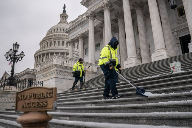Workers clean snow from the steps of the U.S. Capitol as a winter storm passes through the Northeast corridor in Washington, D.C., on Thursday. Photo by Ken Cedeno/UPI