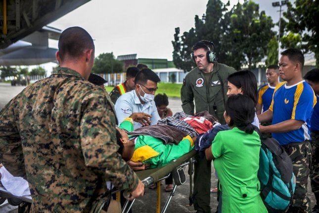 U.S. Marine Staff Sgt. Jacques Mason, U.S. Marine Cpl. Zachery Stapf, help offload an injured Filipino civilian out of a Marine C-130 Hercules aircraft at Villamor Air Base, in the Philippines, November 12, 2013 as they assist in relief efforts in the wake of Typhoon Haiyan. UPI/Codey Underwood/USMC