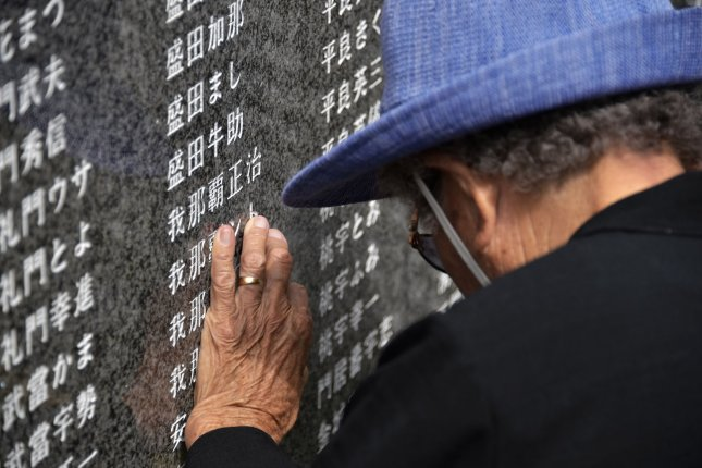 Worshippers pray for victims in front of the monument Cornerstone of Peace of the battle of Okinawa at the Peace memorial park in Itoman, Okinawa, Japan, on June 23. Japan's elderly population is growing, and crime cases involving senior citizens are on the rise, according to police. Photo by Keizo Mori/UPI