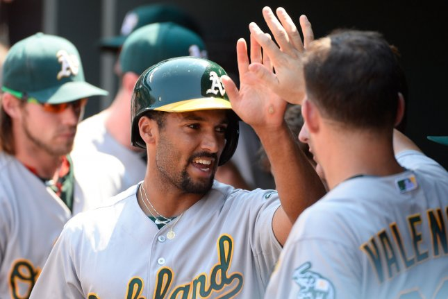 Oakland Athletics' Marcus Semien is congratulated in the dugout by Danny Valencia. Photo by David Tulis/UPI