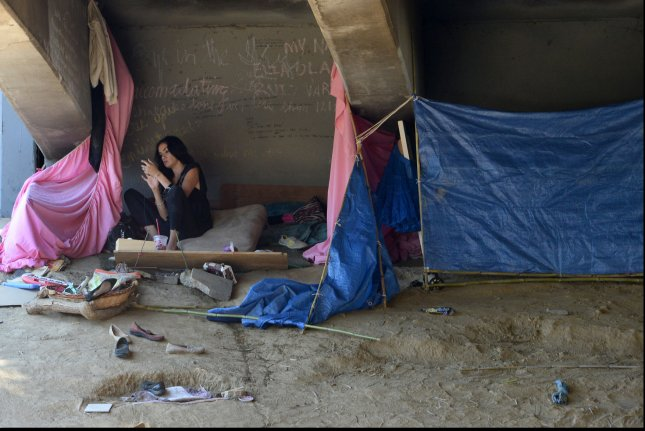 A woman is seen in a makeshift shelter beneath the Hollywood Freeway in Los Angeles. A United Nations report delivered Friday said more than 40 million people in the United States live in poverty. File Photo by Jim Ruymen/UPI