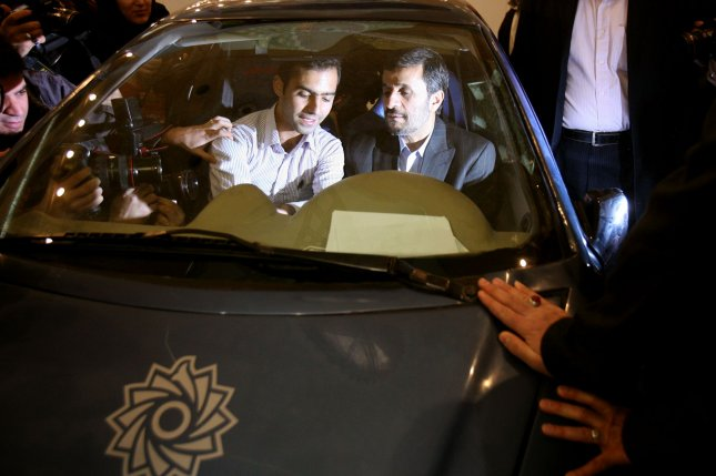 A Shahid Rajai University student speaks to Iranian President Mahmoud Ahmadinejad as they sits in an electric vehicle of the 2nd National Festival of Innovation and Prosperity in Tehran, Iran on February 8, 2010. Ahmadinejad said on Sunday that Iran will start the controversial process of enriching its uranium to 20 percent. UPI/Maryam Rahmanian