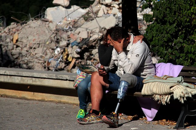 Italians sit next to the rubble and debris after an earthquake in the central Italian town of Amatrice on Saturday. The government said 290 people were killed when a 6.2-mgnitude earthquake hit the region on Wednesday. Photo by Marco D'Antonio/ UPI