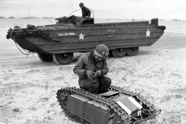 A member of the the U.S. Navy's Second Beach Battalion disassembles a German Beetle remote-controlled miniature explosive tank on Utah Beach on June 11, 1944. These vehicles were built as mobile anti-landing craft mines. Photographed by Combat Photo Unit Eight (CPU-8). Note the DUKY in the immediate background. Photo by U.S. Navy/National Archives/UPI