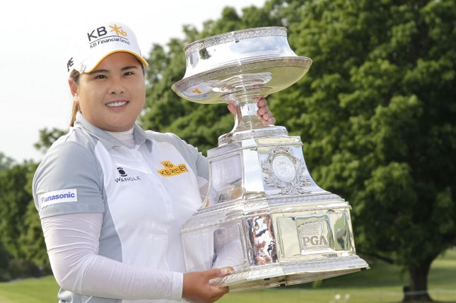 Inbee Park of Korea holds the championship trophy on the 18th green after the final round of the KPMG Women's PGA Championship at Westchester Country Club in Harrison, NY on June 14, 2015. Photo by John Angelillo/UPI