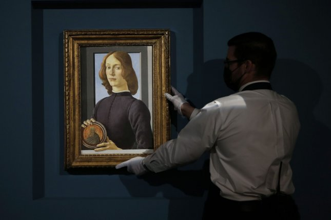 A painting by Sandro Botticelli called Young Man Holding a Roundel is held by a Sotheby's employee Friday in New York City. Photo by John Angelillo/UPI