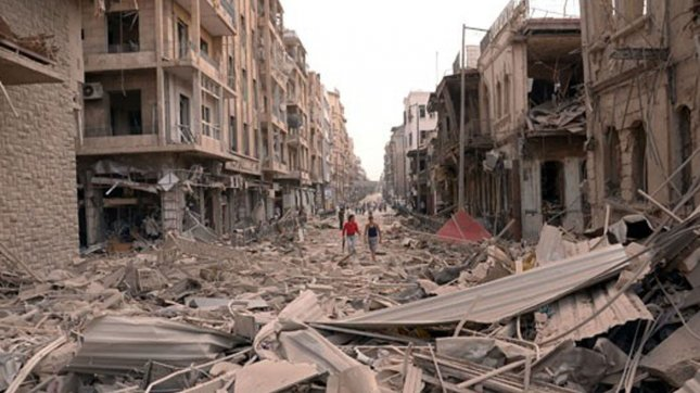 In this photo released by the Syrian official news agency SANA, Syrians walk through the rubble at the scene where multiple bombs explosions hit the center of Aleppo, Syria on October 3, 2012. UPI