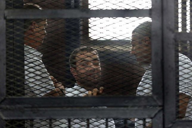 Three Al Jazeera journalists, left to right, Australian Peter Greste, Baher Mohamed and Canadian-Egyptian Mohamed Fahmy stand behind caged bars with other defendants as they listen to the ruling at a court in Cairo, Egypt last June. The three were sentenced to seven years in prison on terrorism-related charges. The ruling brought worldwide criticism of the Egyptian court system. File Photo by Karem Ahmed/UPI