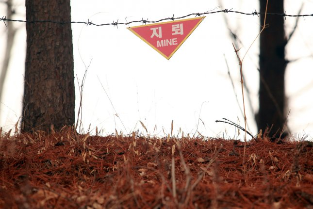 A mine field warning sign hangs in part of the Demilitarized Zone (DMZ) near Seoul in 2013. A land mine explosion on Tuesday critically injured two South Korean soldiers on routine patrol. File Photo by Stephen Shaver/UPI