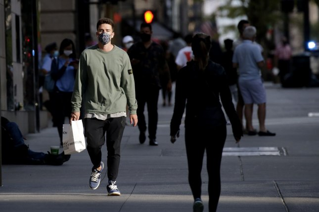 Pedestrians wear face masks to protect from and prevent the spread of COVID-19 as they walk on the sidewalks of Fifth Avenue in New York City. Photo by John Angelillo/UPI