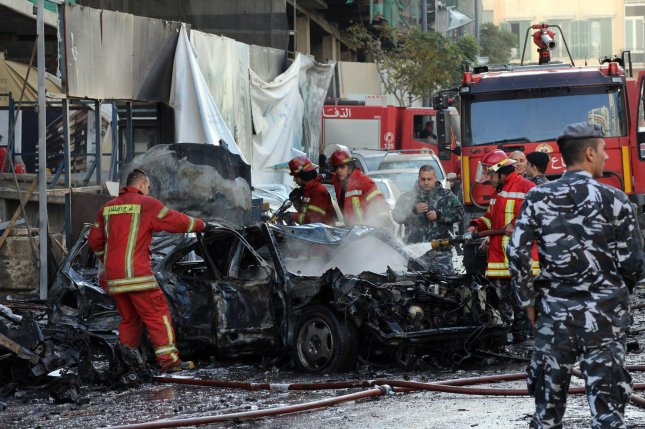 Fire and police officials gather at the site of an explosion in downtown Beirut that killed at least five people, including former Lebanese Minister Mohamad Chatah, on December 27, 2013. Chatah, who is a vocal opponent of Syrian President Bashar al-Assad, was killed in a massive bomb blast that targeted his car convoy. More that 70 people were injured. UPI/Mohamad Sultan