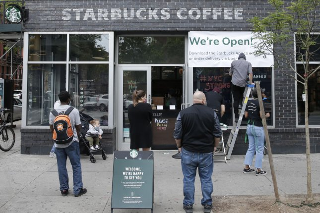Customers wait outside as workers hang a We're Open sign at a Starbucks Coffee franchise in Manhattan Thursday. A report said that consumer spending fell more than 13 percent in April. Photo by John Angelillo/UPI